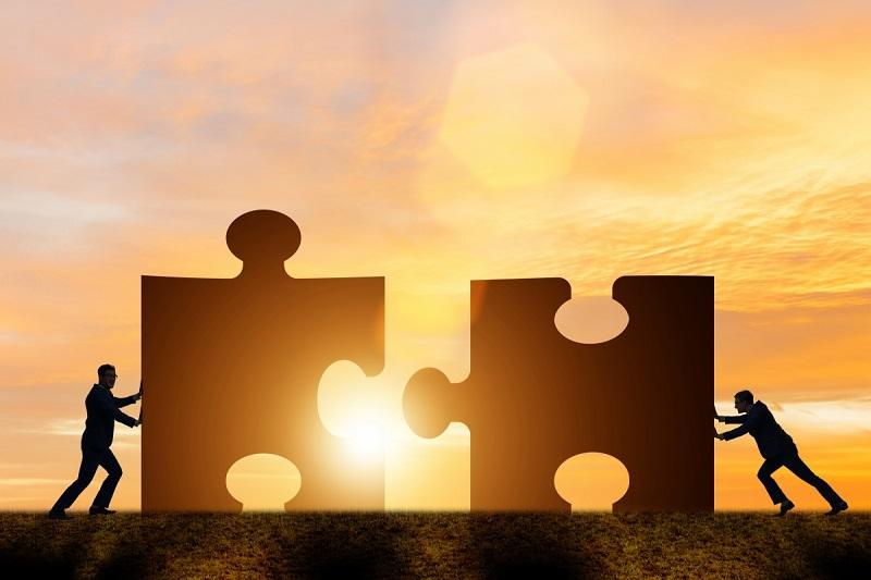 Zwei Männer, die zwei Puzzle ineinander schieben